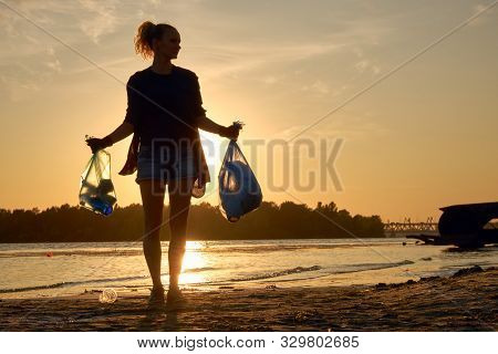 Young Girl In Black Gloves Is Walking With Garbage Bags Along A Dirty Beach Of The River And Cleanin