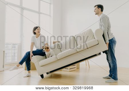Indoor Shot Of Funny Family Couple Furnish Their First Home, Carry Big White Sofa, Woman Teases Dome