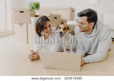 Lovely Just Married Couple Lie On Floor, Use Laptop Computer, Creats Design Project For New House, T