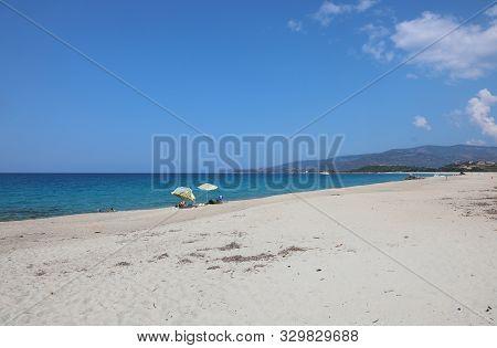 Beach Of An Europea Island With Sunshade And The Mediterranean Sea