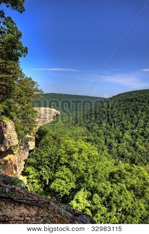 This famous place on the Whitaker's Point trail is the number 1 most photographed spot in Arkansas. A male hiker enjoys the view standing hundreds of feet above the Ozark mountains forest below. poster