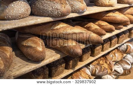 Assortments Of Bread, Freshly Baked On Wooden Shelves. Piles Of Breads. Bakery Shelves Full Of Bread