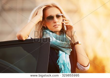 Young fashion blonde business woman talking on cell phone leaning on car door Stylish female model in sunglasses and blue scarf