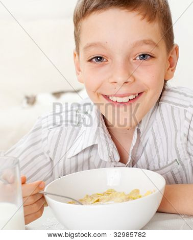 Child eating frosted flakes at breakfast