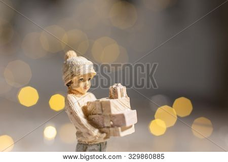 Decorative Christmas-themed Figurines. Statuette Of A Girl Holding Boxes With Gifts For Christmas In