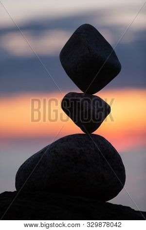 balanced stones on the beach at sunset