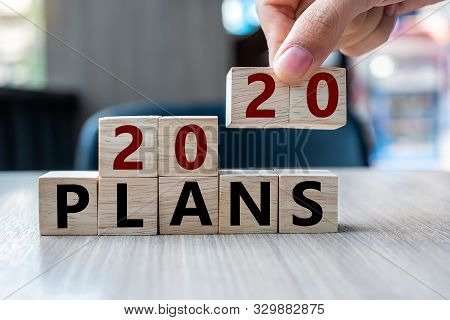 Business Man Hand Holding Wooden Cube With 2020 Plans Word On Table Background. Resolution, Strategy