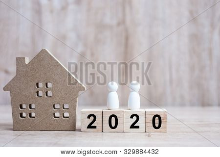 2020 Happy New Year With House Model And People  On Wooden Background. Banking, Real Estate, Investm