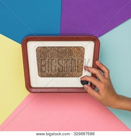 The Hand Adjusts The Volume Of The Vintage Radio On A Colored Background. Radio Engineering Of The P
