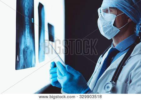 Doctor in hospital sitting at desk looking at x-rays on tablet against white background with x-rays