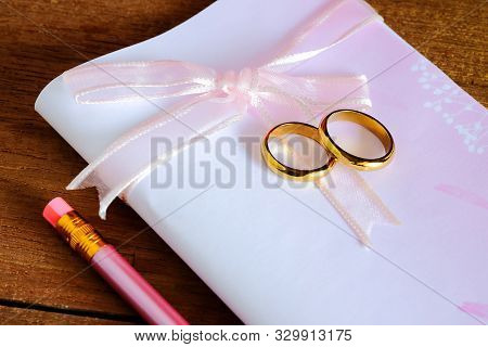 Duo Golden Wedding Ring Over Invice Card On Wood Table.wedding Concept.