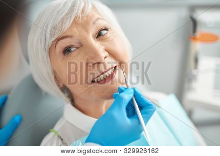 Close Up Of Smiling Elderly Lady At The Dentist Office