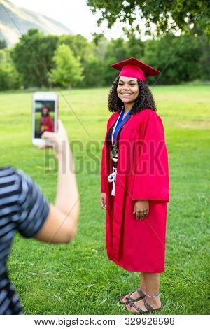 Taking a smartphone photo of a recent high school graduate in her cap and gown. Full length candid photo of a cute smiling diverse girl of African descent.