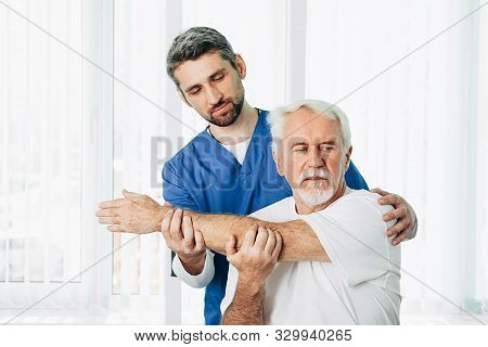 Senior Patient While Exercise Treatment With His Physiotherapist. Rehab At Medical Center