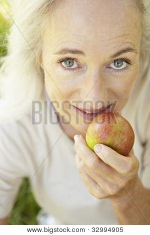 Senior woman eating apple outdoors