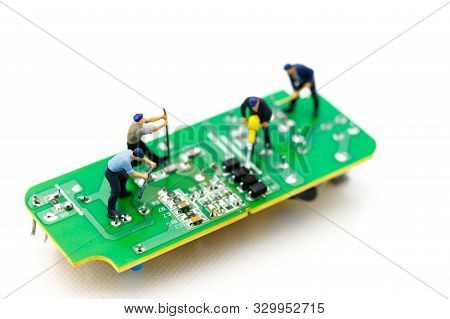 Miniature People: Engineers Fixing Error On Chip Of Circuit Board. Computer Repair Concept.