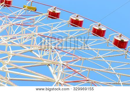 The Big Ferris Wheel Moves. Bright Photo Of The Amusement Park. Red Cabins Against A Clear Blue Sky.