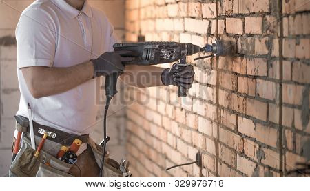 Handyman Uses Jackhammer, For Installation, Professional Worker On The Construction Site. The Concep