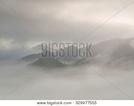 Rocky Gulch Full Of Heavy Dark Fog  Above Deep Forest. Cold Sun Hidden In Heavy Clouds.
