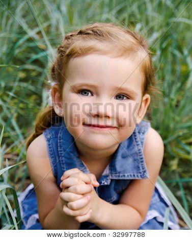 Retrato de sonriente niña vestida al aire libre