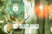 Writing note showing Set Smart Goals. Business photo showcasing giving criteria to guide in the setting of objectives Female human wear formal work suit presenting smart device. poster