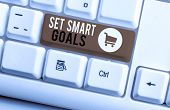 Word writing text Set Smart Goals. Business concept for giving criteria to guide in the setting of objectives White pc keyboard with empty note paper above white background key copy space. poster