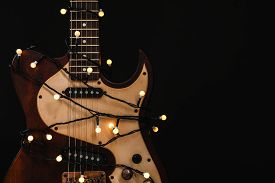 Guitar With Golden Lights On Black Background, Space For Text. Christmas Music