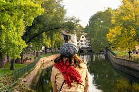 Woman Relaxing On Bridge In Strasbourg. Vacations Lifestyle. Woman Looking To River .vacation Lifest