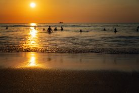 Silhouettes Of People In The Sea At Sunset. Thailand, Phuket, Karon Beach