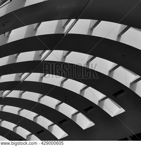A curved ceiling of a huge building. An abstract black and white photo of an interior building.