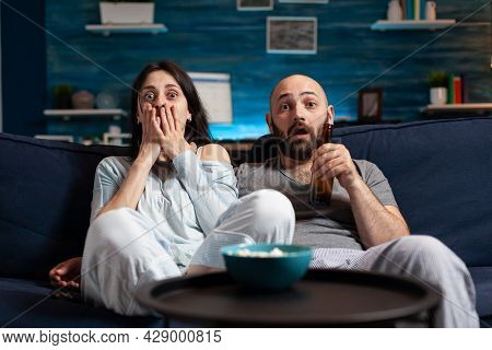 Shocked Confused Young Couple Watching Documentary Movie At Tv Having Astonished Facial Expression,