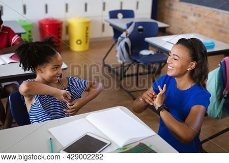 African american female teacher and a girl talking in hand sign language at elementary school. school and education concept