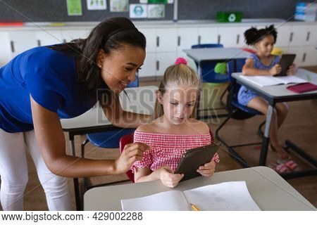 African american female teacher teaching a girl to use digital tablet in class at elementary school. education back to school health safety during covid19 coronavirus pandemic