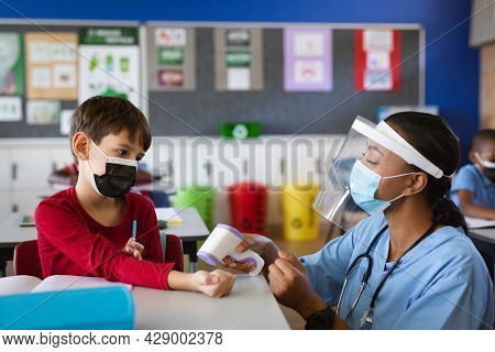 Female health worker wearing face shield measuring temperature of a boy at elementary school. education back to school health safety during covid19 coronavirus pandemic.