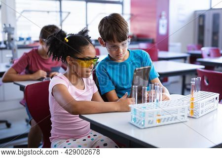 African american girl and caucasian boy using digital tablet in science class at elementary school. school and education concept