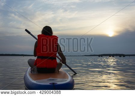 A Teenage Girl Swims On A Sup Board, A Beautiful Girl Rides A Board With A Paddle On A Beautiful Lak