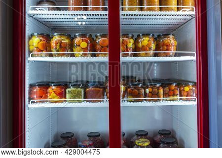 A Refrigerated Display Case With Cans Of Canned Home Products, A Refrigerator With Canned Fruits And