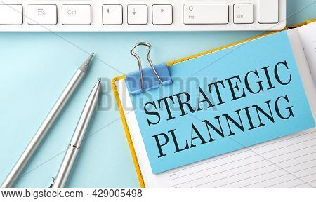 Strategic Planning Text On Sticker On Blue Background With Pen And Keyboard