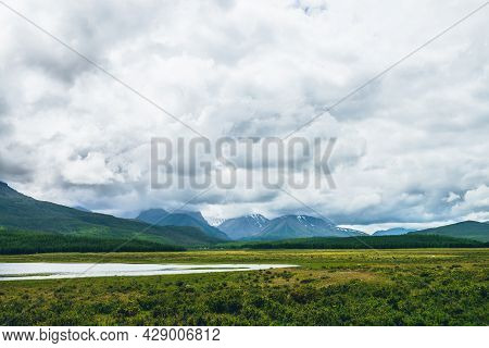 Dramatic Landscape With Mountain Lake And Forest On Hills In Sunlight And Snowy Mountains In Low Clo