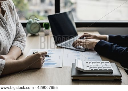Two Staff Members Of The Finance Department Are Sharing Monthly Financial Statements Together, They
