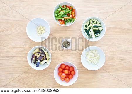 Ingredients: Vegetables For Ratatouille In White Bowls On A Wooden Table Background. Peppers, Tomato