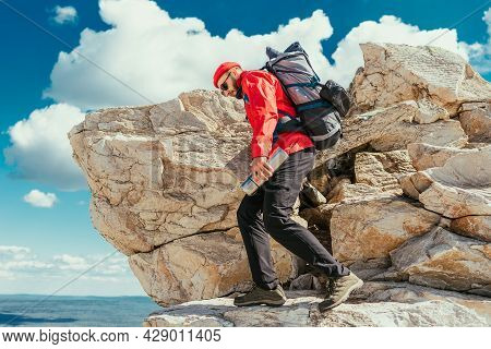 A Traveler Among The Rocky Mountains. A Man Is A Traveler With A Backpack Among The Rocks. Backpacki