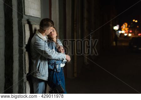 Guy Tender Hugs His Girlfriend, Evening Date In The City. Young Loving Couple On The Street. Evening