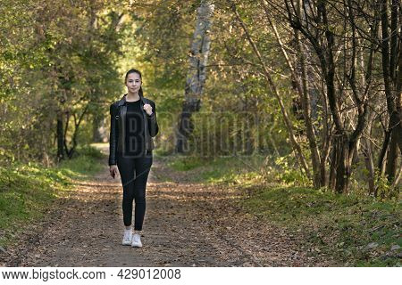 Beautiful Young Woman Walks In The Autumn Park. Happy Girl In Black Clothes In The Forest. Alley, Pr