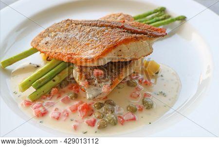 Plate Of Pan Seared Sea Bass With Tomato Caper Mustard Cream Sauce