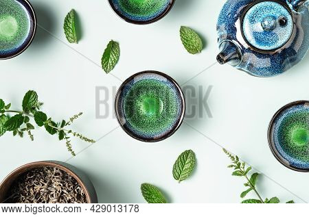 Green Tea In A Dark Blue Clay Teapot And Small Cups On Pastel Blue Background With Mint Leaves Decor
