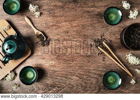 Dark Turquoise Glazed Clay Teapot And Small Cups On Dark Wooden Background Decorated With White Flow