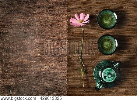 Dark Turquoise Glazed Clay Teapot And Small Cups On Dark Wooden Background With Bamboo Mat Decorated