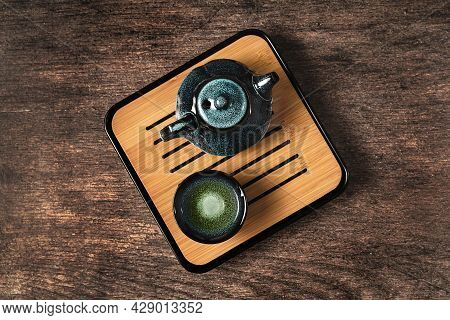 Dark Turquoise Glazed Clay Teapot And Small Cup On Dark Wooden Background. Flat Lay Style.