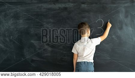 Pupil In Class At A Math Lesson Writes On A Chalk Board With Chalk. Elementary School Math Lesson. L